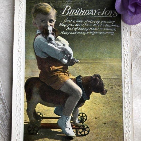 画像1: Postcard  犬のプルトイのおもちゃに乗る子犬を抱いた男の子 イギリス (1)